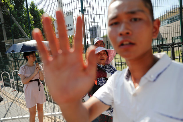 A security agent gestures near the site of a blast outside the U.S. embassy in Beijing, China July 26, 2018. (Photo by Damir Sagolj/Reuters)