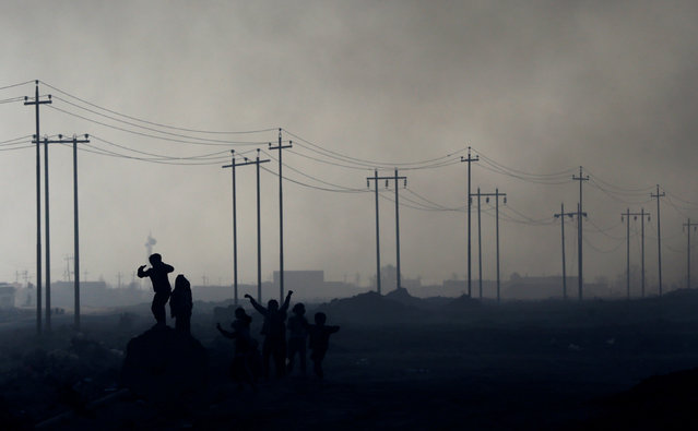 Children play in front of oilfields burned by Islamic State fighters in Qayyara, south of Mosul, Iraq November 23, 2016. (Photo by Goran Tomasevic/Reuters)