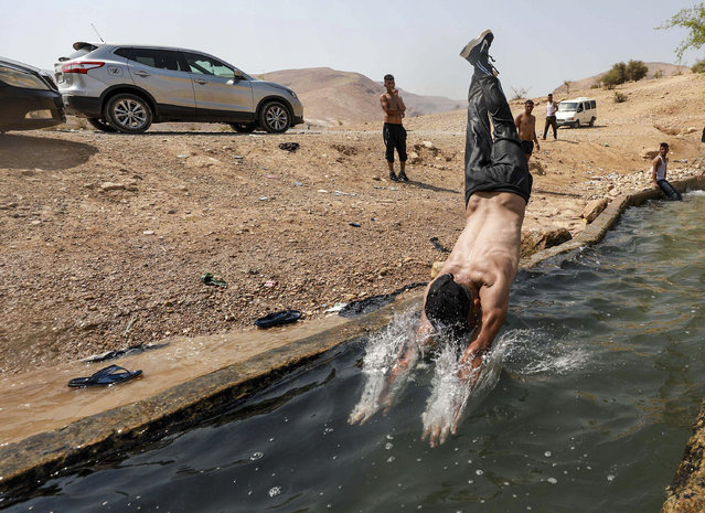Children and youth cool off in irrigation channel on a hot day in Al-Auja town of Jericho, West Bank on September 08, 2020. (Photo by Issam Rimawi/Anadolu Agency via Getty Images)