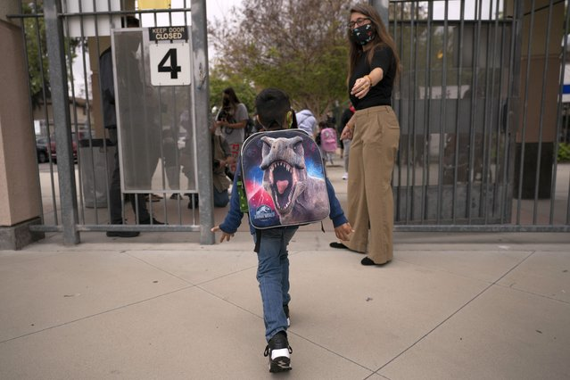 """Kindergartener Angel Hernandez leaves after the first day of in-person learning at Maurice Sendak Elementary School in Los Angeles, Tuesday, April 13, 2021.  A recent spike in coronavirus cases in some states has led one of the nation's top health experts to suggest that governors could """"close things down"""" like they did during previous surges. But that doesn't appear likely to happen – not even in states led by Democratic governors who favored greater restrictions in the past. (Photo by Jae C. Hong/AP Photo)"""