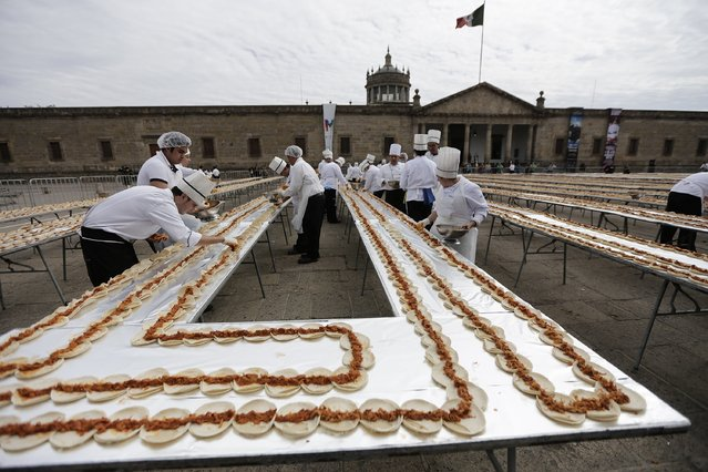 Chefs prepare tacos of Cochinita Pibil, a popular dish from Yucatan, in an attempt to break the Guinness World Record for the world's longest taco in Guadalajara February 15, 2015. (Photo by Alejandro Acosta/Reuters)