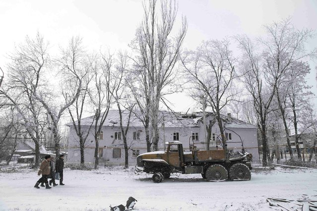 Locals walk past a destroyed Ukrainian army truck in the town of Vuhlehirsk, about 10 km (6 miles) to the west of Debaltseve, February 16, 2015. (Photo by Baz Ratner/Reuters)