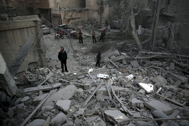 Residents inspect damage in a site hit by what activists said were airstrikes carried out by the Russian air force in the town of Douma, eastern Ghouta in Damascus, Syria January 10, 2016. (Photo by Bassam Khabieh/Reuters)