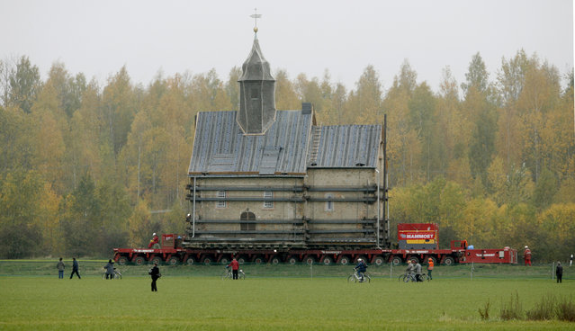 The Emmaus church is transported on a special trailer, after leaving the eastern German village of Heuersdorf October 25, 2007. The church, built in 1297, will be moved over 12 kilometres to the neighbouring town of Borna, as Heuersdorf has to give way for the extension of an opencast lignite mine. (Photo by Arnd Wiegmann/Reuters)