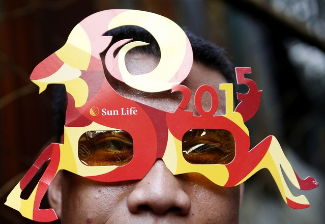 A reveller wears a mask to celebrate Lunar New Year at Manila's Chinatown February 19, 2015. (Photo by Erik De Castro/Reuters)