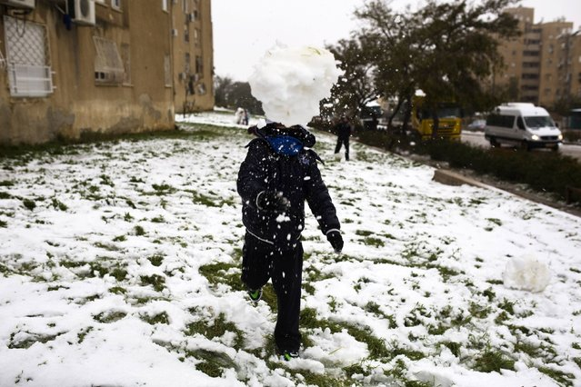 A youth throws a snowball as he plays in the southern Israeli city of Arad February 20, 2015. (Photo by Amir Cohen/Reuters)