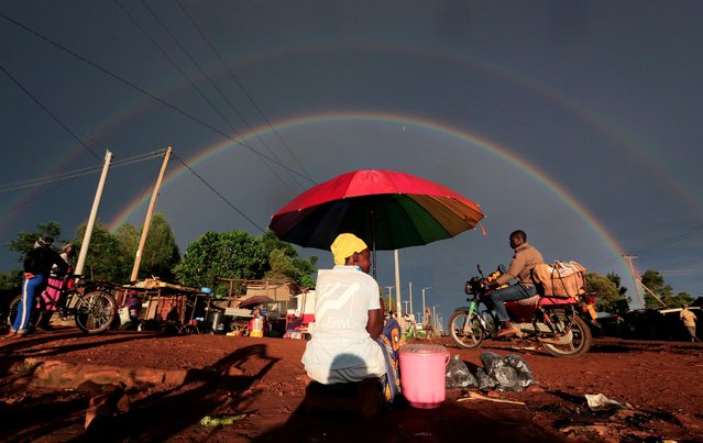 A double rainbow is seen above a woman holding an umbrella and selling snacks along the road in Siaya county, Kenya on May 3, 2020. (Photo by Thomas Mukoya/Reuters)