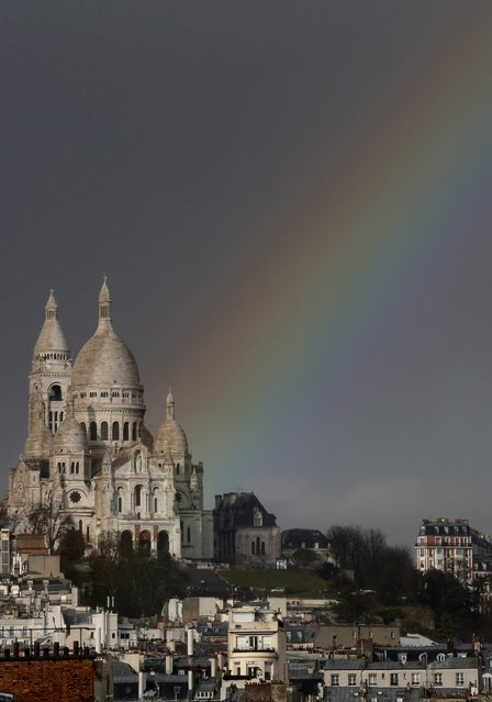 A rainbow is seen against rain clouds above the Sacre Coeur Basilica on Montmartre after a sudden rain shower hit Paris February 23, 2015. (Photo by Christian Hartmann/Reuters)