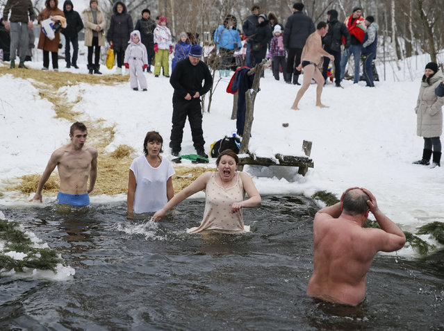 People react as they take a dip in a lake during Orthodox Epiphany celebrations in Kiev, Ukraine, January 19, 2016. (Photo by Gleb Garanich/Reuters)