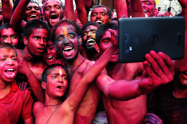 epa04649961 Indian revellers smeared with colors take selfies during the Holi Festival in Bangalore, India, 06 March 2015. Holi is celebrated at the end of the winter season on the last full moon day of the lunar month Phalguna (February or March) and its main day is celebrated by people throwing colored powder and colored water at each other.  EPA/JAGADEESH NV