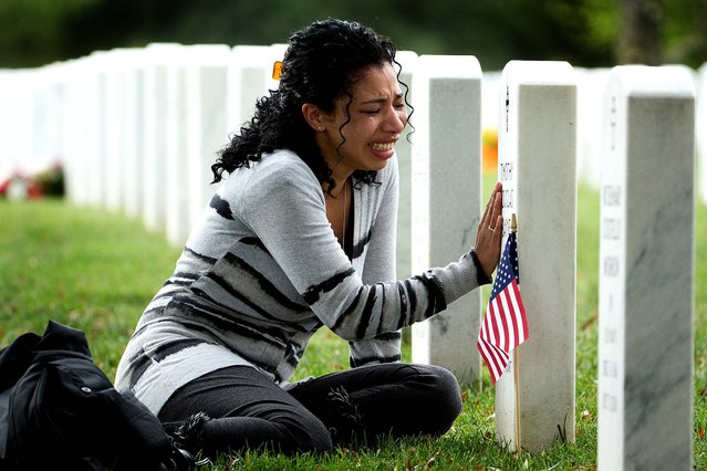 Thania Sayne of Effingham, Illinois, cries at the grave of her husband, Army Sgt. Timothy D. Sayne, during the playing of taps at a nearby burial service at Arlington National Cemetery, a day before what would have been their third wedding anniversary.  Sayne was 4 months pregnant with their second son, Douglas, when her husband was killed on Sept. 18, 2011, in the Kandahar province of Afghanistan. (Photo by Manuel Balce Ceneta/Associated Press)