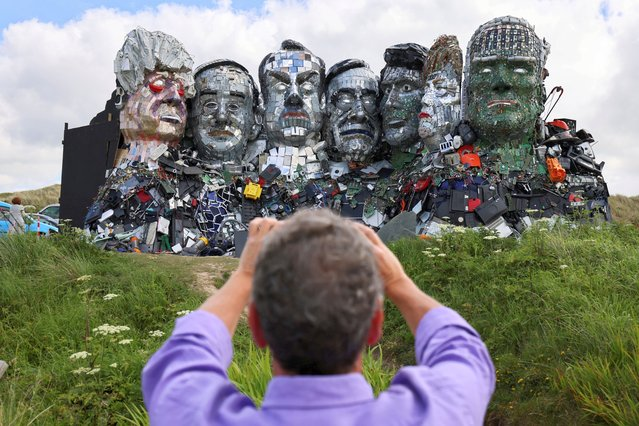 """A man photographs """"Mount Recyclemore"""", an artwork depicting the G7 leaders looking towards Carbis Bay, made from electronic waste by Joe Rush and Alex Wreckage, ahead of the G7 summit, at Hayle Towans in Cornwall, Britain, June 8, 2021. (Photo by Tom Nicholson/Reuters)"""