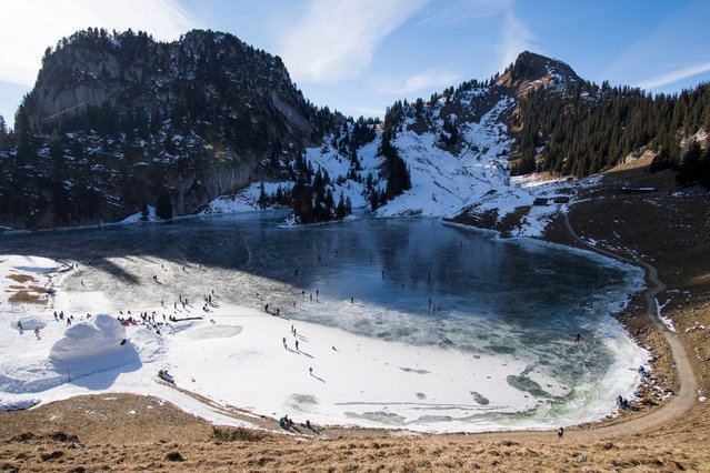 People enjoy ice skating on the black ice of the Hinterstockensee, above Erlenbach in the Simmental valley, Canton of Bern, Switzerland, 17 December 2016. (Photo by Anthony Anex/EPA)