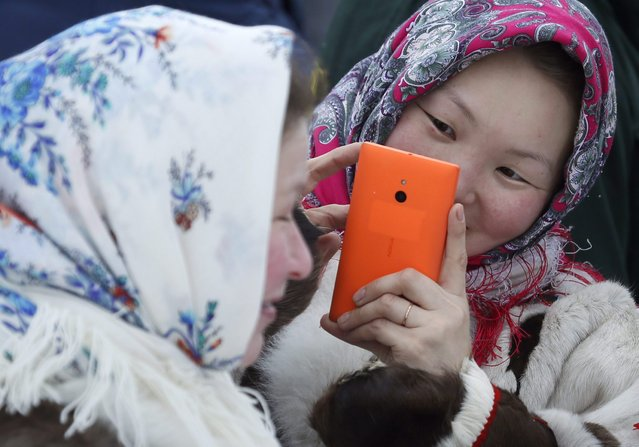 In this photo taken on Saturday, March 14, 2015, Nenets women take photos as they attend the Reindeer Herder's Day holiday in the city of Nadym, in Yamal-Nenets Region, 2500 kilometers (about 1553 miles) northeast of Moscow, Russia. (Photo by Dmitry Lovetsky/AP Photo)