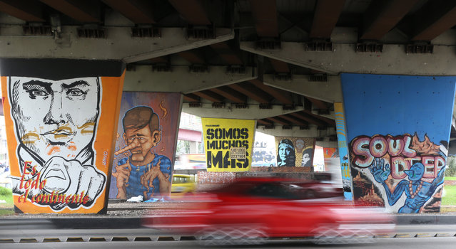 In this March 18, 2015 photo, a car speeds past backdropped by overpass supports covered with street art, in Bogota, Colombia. (Photo by Fernando Vergara/AP Photo)
