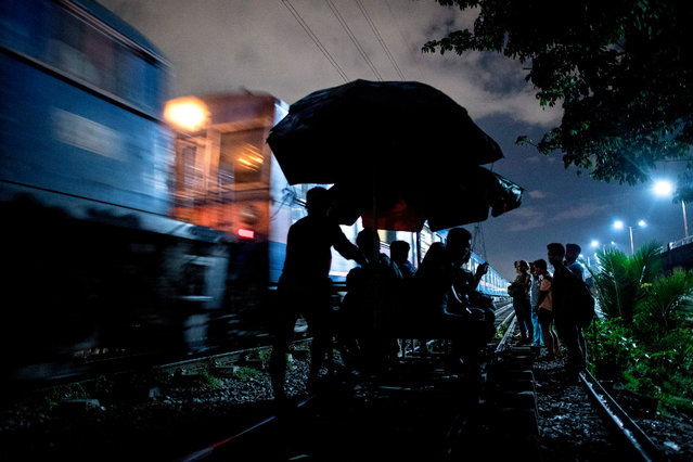 """This picture taken on October 18, 2018, shows """"trolley boys"""" with passengers along a train track as a train passes by in Manila, Philippines. (Photo by Noel Celis/AFP Photo)"""