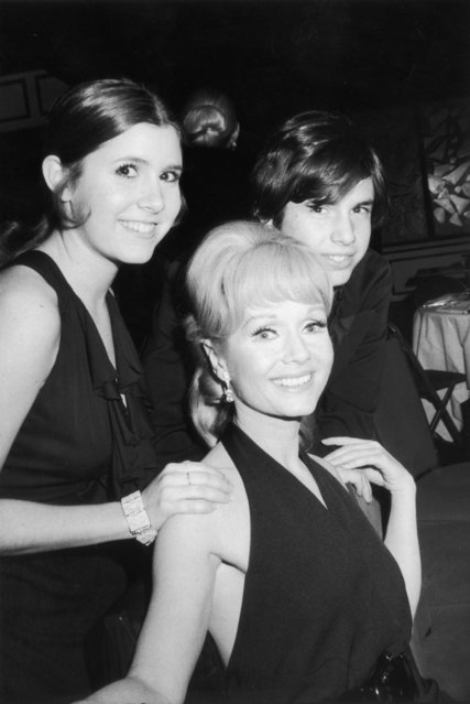 """American actor Debbie Reynolds sits and smiles with her children, actor Carrie Fisher and Todd Fisher, as they attend the opening night party for the Broadway musical revival """"Irene"""", in which Reynolds starred, New York City, 13th March 1973. The music was composed by Hal Tierney, with lyrics by Joseph McCarthy. (Photo by Tim Boxer/Hulton Archive/Getty Images)"""