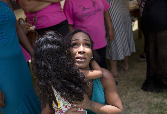 An inmate holds her daughter during the 13th annual Miss Talavera Bruce beauty pageant at the penitentiary the pageant is named for, in Rio de Janeiro, Brazil, Tuesday, December 4, 2018. The event aims to improve the women's self-esteem and is an opportunity to unite with family members they seldom see. (Photo by Silvia Izquierdo/AP Photo)