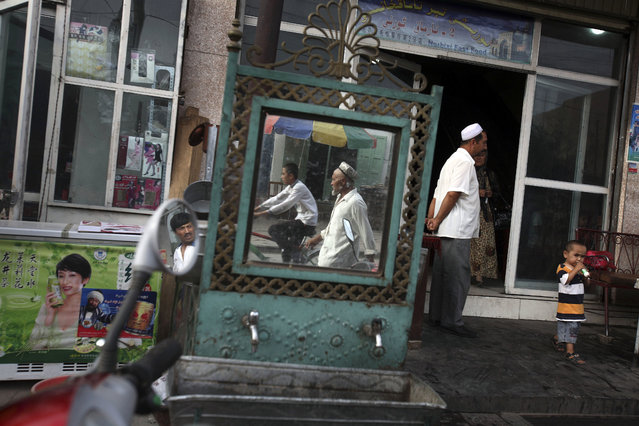 """In this August 6, 2008, file photo, Uighurs are seen outside a restaurant in Kashgar in China's western Xinjiang province. More than a million Chinese civil servants have been assigned to move into the homes of Uighurs and other ethnic minorities, spending weeks as uninvited guests. While government notices about the """"Pair Up and Become Family"""" program portray it as an affectionate cultural exchange, exiled Uighurs living in Turkey said their loved ones saw the campaign as a chilling intrusion, aimed at coercing Uighurs into living secular lives like the Han majority. (Photo by Ng Han Guan/AP Photo)"""