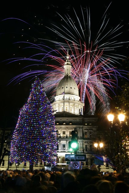 Fireworks explode over the state Capitol following a ceremony lighting the official state Christmas tree in Lansing, Michigan. (Photo by Al Goldis/Associated Press)