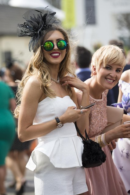 Spectators smile during Aintree race meeting's Ladies Day the day before the Grand National horse race at Aintree Racecourse Liverpool, England, Friday, April 10, 2015. (Photo by Jon Super/AP Photo)