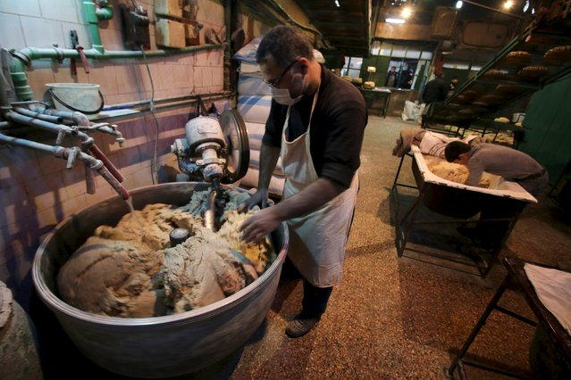 A man and his son prepare dough inside a bakery in the rebel held al-Shaar neighborhood of Aleppo, Syria, February 10, 2016. (Photo by Abdalrhman Ismail/Reuters)