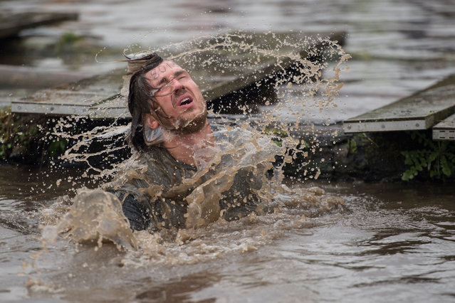 A competitor emerges from muddy water as he negotiates a water obstacle in the Tough Guy endurance event near Wolverhampton, central England, on January 27, 2019. (Photo by Oli Scarff/AFP Photo)
