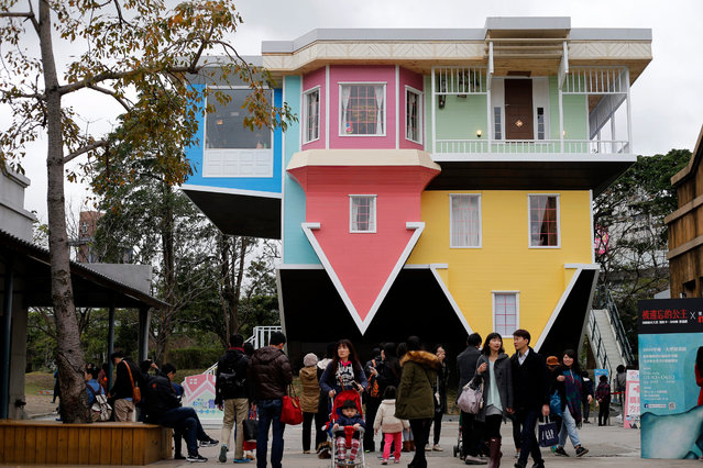 Visitors visit the upside-down family size house in Taipei, Taiwan, 23 February 2016. The three story upside-down family size house attracts hundreds of visitor's who are amused with the exhibit. According to the organizers, the total cost of the construction is around 600,000 US Dollars and took 2 months to complete. (Photo by Ritchie B. Tongo/EPA)