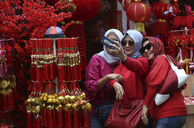In this Monday, January 28, 2019, photo, Muslim women take a selfie at a shop selling Lunar New Year decorations in the Chinatown area of Jakarta, Indonesia. People of Chinese descent in the world's most populous Muslim country are preparing to celebrate the Lunar New Year of the Pig on Feb. 5. (Photo by Achmad Ibrahim/AP Photo)