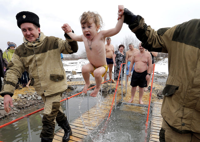 An Orthodox child is given an icy dip in a lake in celebration of Epiphan, near the village of Vorontsovka, some 20 km from the Kyrgyz capital of Bishkek, Kyrgyzstan, 19 January 2019. People believe that bathing in blessed waters during the holiday of Epiphany strengthens their spirit and body. (Photo by Igor Kovalenko/EPA/EFE)