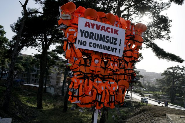 """Life jackets and shoes left by refugees and migrants on Turkish beaches, during their attempts of crossing to the Greek islands, are displayed on a main road leads to Ayvacik, a coastal town in Gallipoli district, Turkey, March 2, 2016. Letters read in Turkish reads """"Ayvacik. No comment"""". (Photo by Umit Bektas/Reuters)"""