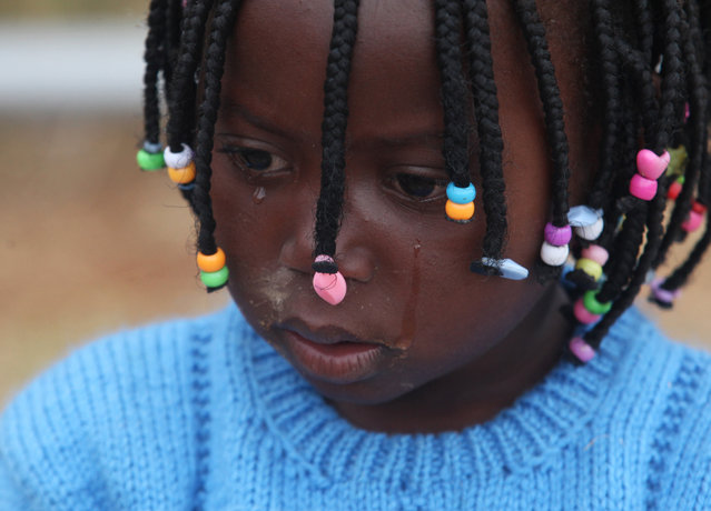A child weeps at a shelter for victims of immigrant attacks in Johannesburg, Wednesday, April 22, 2015. No new incidents of violence targeting foreigners were reported overnight in Johannesburg or in the coastal city of Durban, where the attacks began, police said. (Photo by Denis Farrell/AP Photo)