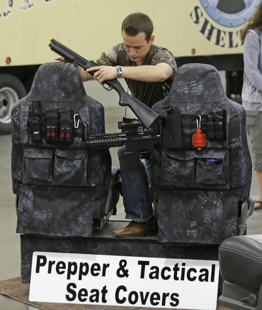 Niel Burnett, of Covers & Camo, demonstrates a seat cover during the PrepperCon expo Friday, April 24, 2015, in Sandy, Utah. (Photo by Rick Bowmer/AP Photo)