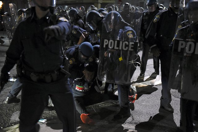Law enforcement officers detain a demonstrator on Gilmore Avenue near Baltimore Police Department Western District during a protest against the death of Freddie Gray in police custody, in Baltimore April 25, 2015. (Photo by Sait Serkan Gurbuz/Reuters)