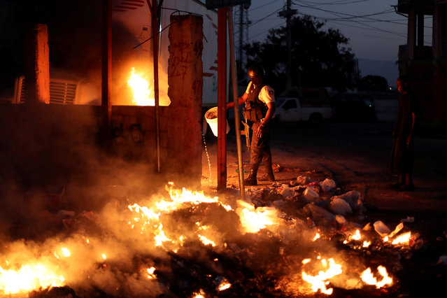 A policeman tries to put out burning garbage used to block a street as part of anti-government protests in Port-au-Prince, February 18, 2019. (Photo by Ivan Alvarado/Reuters)