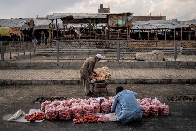 An Afghan man sells fruit on a street in Kabul, Afghanistan, Wednesday, September 22, 2021. (Photo by Bernat Armangue/AP Photo)