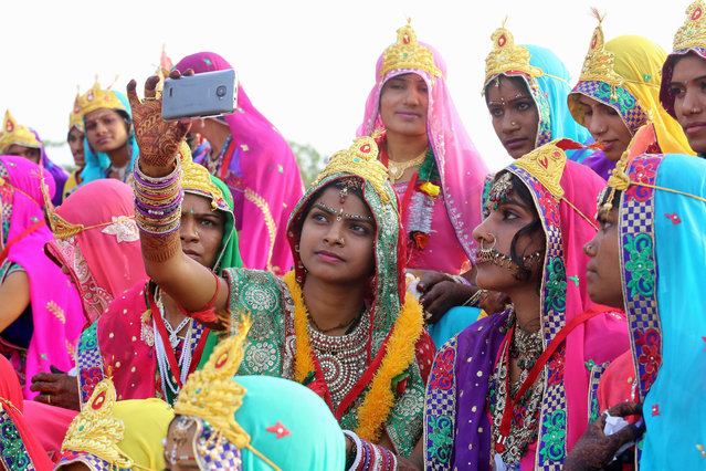 Brides of the Pal community take a selfie with a cell phone during a procession before a mass marriage ceremony on the occasion of Akshaya Tritiya festival in Bhopal, India, 21 April 2015. The day is believed to be the most sacred day of marriages in Hindu mythology. More than 35,000 weddings have taken place all over the Mahdya Pradesh state only on the auspicious day. (Photo by Sanjeev Gupta/EPA)