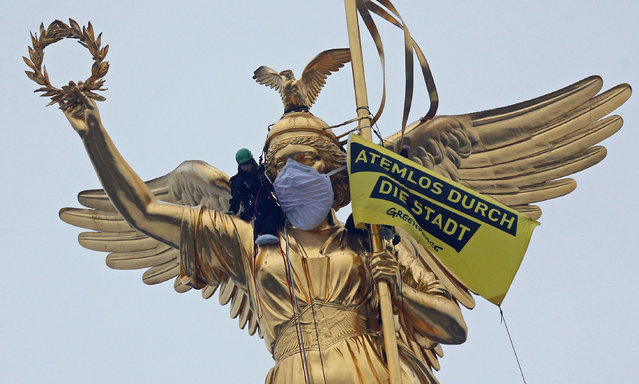 """Greenpeace activists climb the Golden Victoria monument on top of the Victory Column and install a banner """"Breathless through the city"""" to protest against air pollution in Berlin, Germany, January 31, 2017. (Photo by Hannibal Hanschke/Reuters)"""