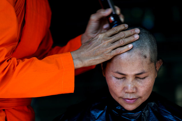 A devotee has her hair cut by a female Buddhist monk during a mass female Buddhist novice monk ordination ceremony at the Songdhammakalyani monastery, Nakhon Pathom province, Thailand, December 5, 2018. Officially, only men can become monks and novices in Thailand under a Buddhist order that, since 1928, has forbidden the ordination of women. A growing number of women defy generations of Thai Buddhist tradition by becoming ordained as novice monks at the unrecognised all-female monastery. (Photo by Athit Perawongmetha/Reuters)