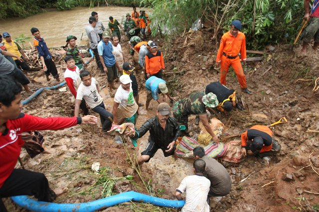 Rescuers search for the victims of a landslide in Jombang, East Java, Indonesia, Tuesday, January 28, 2014. Two landslides triggered by torrential rain killed more than a dozen of people and left some others missing on Indonesia's main island of Java, a government official said Tuesday. (Photo by AP Photo/Trisnadi)