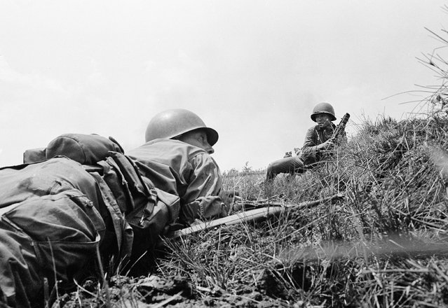 In this April 5, 1965 file photo, Capt. Donald R. Brown crouches on the ground in Saigon, waiting for the order for attack across an open field against Vietcong positions in a treeline from where enemy combatants with automatic weapons had briefly pinned down the HQ company of the 2nd Battalion, 46 Regiment. (Photo by AP Photo)