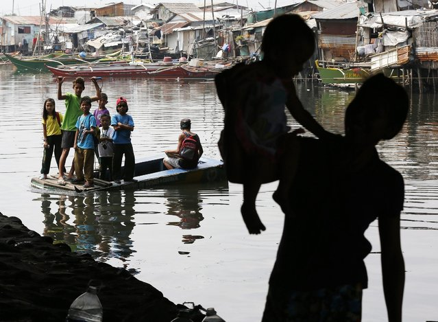 """Filipino school children ride on a makeshift boat as they cross a river in Bacoor, Cavite, Philippines, 11 March 2016. According to Department of Education Secretary Armin Luistro, the government is introducing a story book on disaster preparedness to enhance the awareness and response capabilities of school children to natural and man-made disasters. The book entitled as """"What Happens in Disasters"""" contains a compilation of real accounts of children who survived calamities in the country, Luistro added. (Photo by Francis R. Malasig/EPA)"""