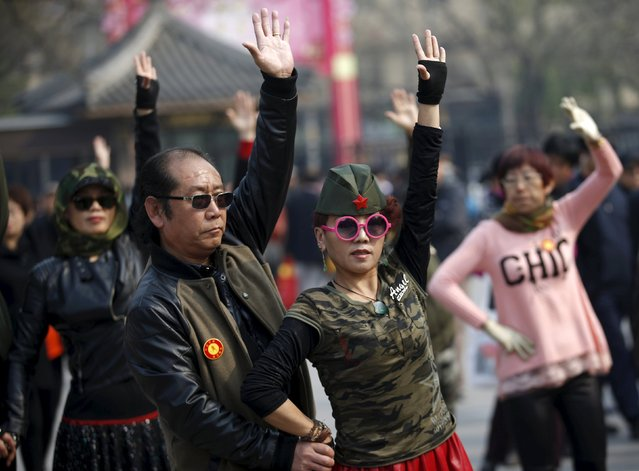 A woman dressed in military style clothes performs square dancing with a man at a park square in Beijing, China, April 9, 2015. (Photo by Kim Kyung-Hoon/Reuters)