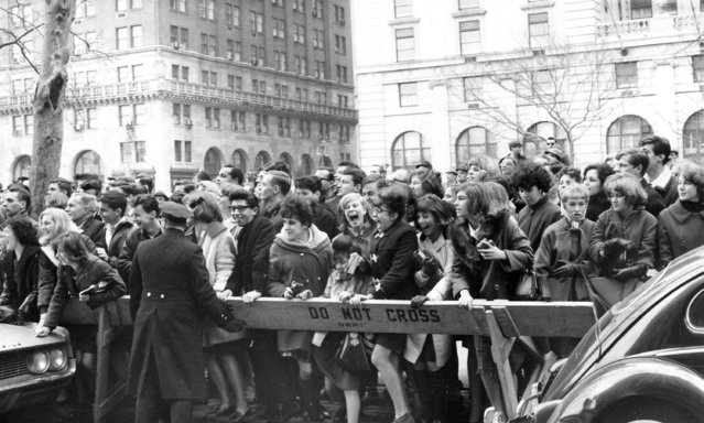 Police enforce the barricades outside New York's Plaza Hotel as fans push forward in hopes of a view of The Beatles after their arrival for an American tour on February 7, 1964. (Photo by AP Photo)