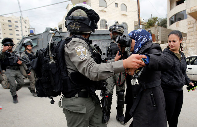 A local photographer takes pictures as an Israeli border police member holds her back during the demolition of a Palestinian house whose owners said they were informed by the Israeli forces that they didn't obtain a construction license, in Beit Jala in the Israeli-occupied West Bank on April 2, 2019. (Photo by Mussa Qawasma/Reuters)