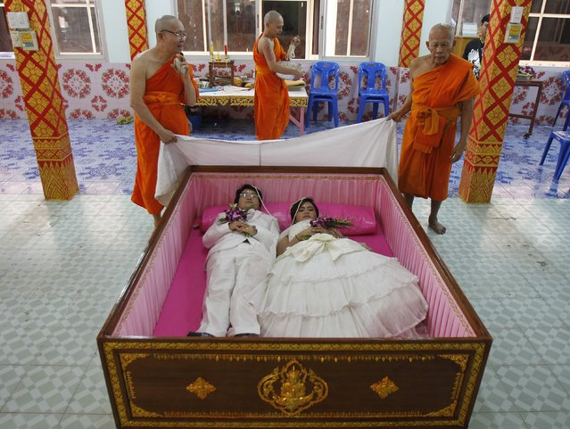Groom Tanapatpurin Samangnitit (bottom L), 40, and his bride Sunantaluk Kongkoon, 26, lie in a coffin during a wedding ceremony at Wat Takien temple in Nonthaburi province, on the outskirts of Bangkok February 14, 2014. Seven Thai couples laid in the pink coffin on Friday during the wedding ceremony organised by the Buddhist temple on Valentine's Day. Couples believe laying briefly in the coffin will get rid of bad luck and usher happiness into their lives. (Photo by Chaiwat Subprasom/Reuters)