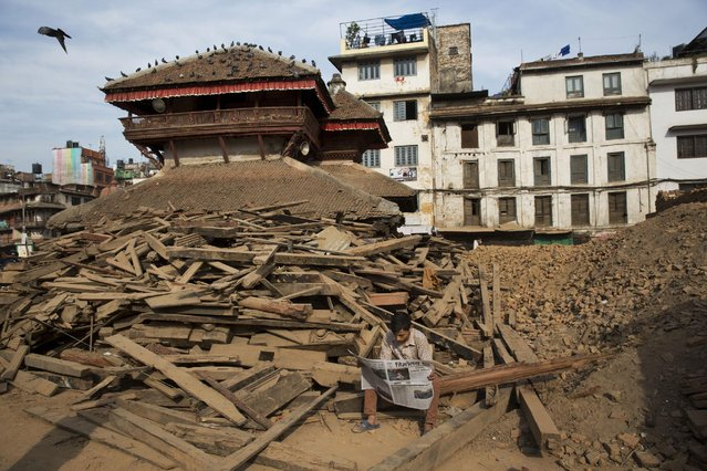 A man reads a newspaper at Basantapur Durbar Square, damaged in the April 25 earthquake in Kathmandu, Nepal, Tuesday, May 5, 2015. (Photo by Bernat Amangue/AP Photo)