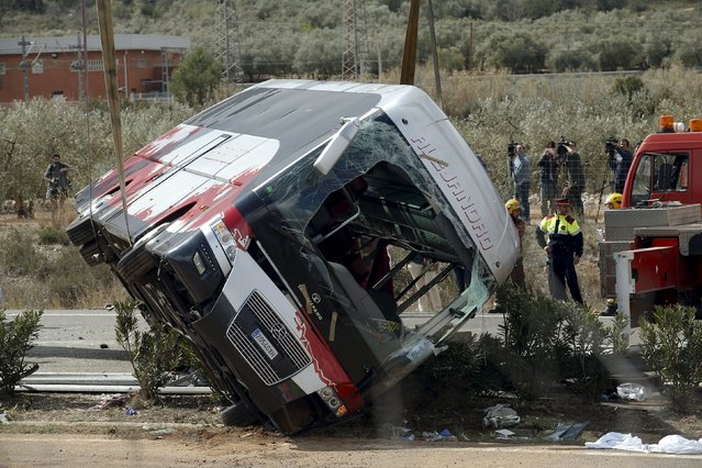 The wreckage of a bus is lifted by a crane after a traffic crash in Freginals, Spain, March 20, 2016. A bus carrying university exchange students back from Spain's largest fireworks festival crashed Sunday on a main highway in the northeast, killing at least 13 passengers and injuring 34 others, officials said. The passengers included Spaniards and foreign nationals from around 20 countries, authorities said. (Photo by Albert Gea/Reuters)