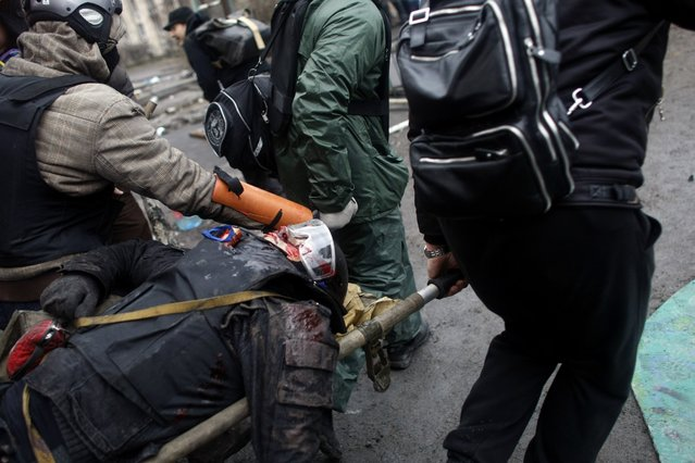 An anti-government protester who sustained a gun shot wound is being carried away to safety on the outskirts of Independence Square in Kiev, Ukraine, Thursday, February 20, 2014. (Photo by Marko Drobnjakovic/AP Photo)