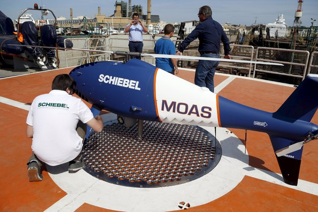 A Migrant Offshore Aid Station (MOAS) crew member looks at a Schiebel Camcopter S-100 drone on board the ship MV Phoenix in Valletta's Grand Harbour, Malta May 2, 2015. The 40-metre ship MV Phoenix, manned by personnel from international non-governmental organisations Medecins san Frontiere (MSF) and MOAS, left Malta on Saturday for a six-month mission to search for and rescue migrants in the Mediterranean. (Photo by Darrin Zammit Lupi/Reuters)